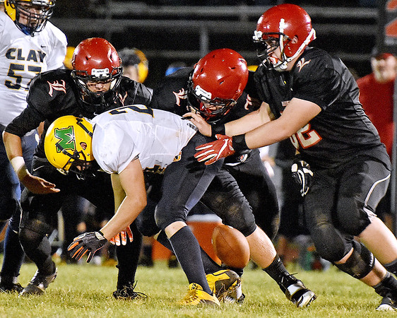 (Brad Davis/The Register-Herald) Liberty defenders (from left) Jacob Bailey, Frank Vanover and Cameron Dillon force Clay County ball carrier Tristen Kent to fumble as they gang tackle him Friday night in Glen Daniel.