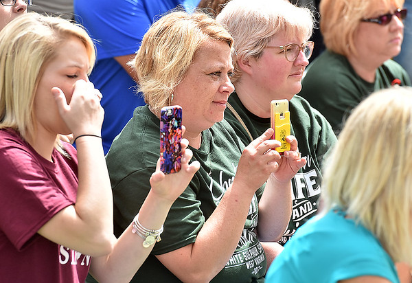 "(Brad Davis/The Register-Herald) Residents look on as singer haley Burns sings ""Smile"" during a somber ceremony for the Old Mill Park Memorial dedication Friday afternoon in White Sulphur Springs"