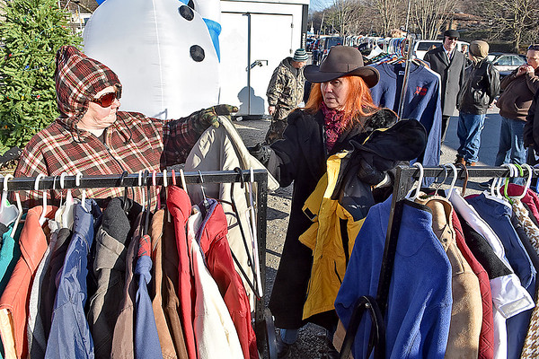 (Brad Davis/The Register-Herald) Volunteer Rose Hicks, far left, helps Sophia resident Deborah Williamson (right of Hicks) as she and others browse through donated coats and other winter clothing being given away for free to anyone in need by members of Sophia United Methodist Church Saturday afternoon in the town's main square.