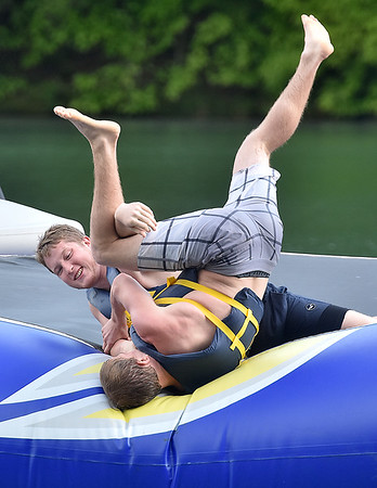 (Brad Davis/The Register-Herald) Life guard Tanner Cantley is tossed from the inflatable as he battles fellow lifeguard Cole Lambert in wrestling match while killing some idle time at Lake Stephens Saturday afternoon.
