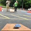 (Brad Davis/The Register-Herald) Residents Julius Mitchell, left, and Ron Clay play a little cornhole during a community picnic at Greenbrier Estates Friday afternoon. Property manager Michelle Bennett, leasing agent Phil Spurlock and other facility officials threw a cook-out style gathering with games for kids and a visit from West Virginia Miners mascot Miner Mike.