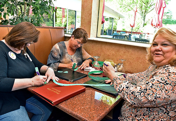(Brad Davis/The Register-Herald) Morgantown residents Kathy Houser, right, and Anndrea Rogers pick up a handful of raffle tickets from Raleigh General Hospital celebrity Debbie Peyton during the opening moments of Celebrity Night at Pasquale's Monday evening.