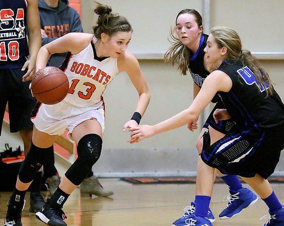 (Brad Davis/The Register-Herald) Summers County's Hannah Taylor looks for a lane along the perimeter as Midland Trail defenders Emily Dickerson, near, and Wilson Jenny apply pressure Thursday night in Hinton.