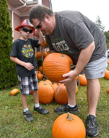 (Brad Davis/The Register-Herald) Scott McGraw picks up a good-sized pumpkin to haul it away after son Ethan McGraw, 6, picks out the perfect one of many during Burlington United Methodist Family Services' annual Pumpkin Festival Sunday afternoon near Prosperity.