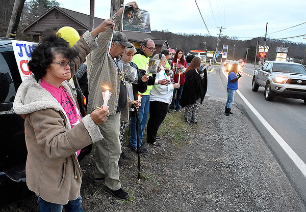(Brad Davis/The Register-Herald) Community members, friends and family stand along the road holding candles and signs for Chaz Richardson, who has been missing since December 3rd of 2015 during a vigil and continued awareness gathering Wednesday evening in Glen Daniel next to the Whitesville State Bank.