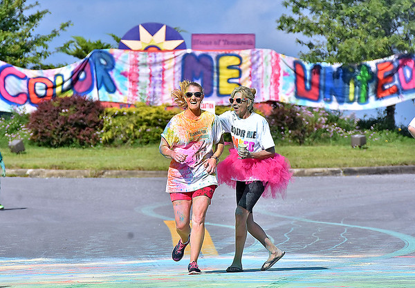 (Brad Davis/The Register-Herald) United Way of Southern West Virginia Executive Director Margaret Ann O'Neal, right, encourages participants while also dousing them in starch during the annual Color Me United Run/Walk Saturday morning at the Raleigh County Memorial Airport.