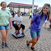 "(Brad Davis/The Register-Herald) Ashley Cross (middle) is bestowed the honor of riding the ""Purple Princess"" as she's pulled by Wendy Acord and escorted by Jade Acord during the American Cancer Society's Relay for Life atop Beckley's Intermodal Gateway Friday night. Anyone chosen to ride the ceremonial toilet was tasked with raising a certain amount of money in donations before they could get off the pot."