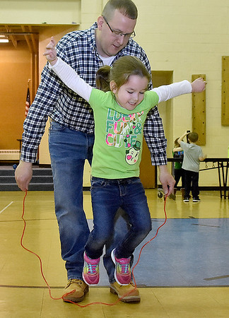 (Brad Davis/The Register-Herald) Four-year-old kindergartener Ashlyn Dunn practices jump roping with the help of her dad Lonnie during Maxwell Hill Elementary's Jumping for Hearts event Friday afternoon in the school's gymnasium. Students spent several days gathering donations for the American Heart Association by sending out e-mails, asking friends and family or even going door-to-door in their neighborhoods if they wised, raising around $5,000 overall. The annual event concluded with a special celebration in the gym where students got to run and play in a variety of jumping-related activities.