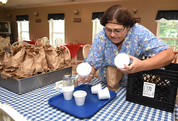 Mona Goodson, packaging up lunches at the Greenbrier County Committee on Aging in Rupert.<br /> (Rick Barbero/The Register-Herald)