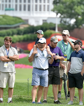 (Brad Davis/The Register-Herald) A young fan gets an adult's view atop his dad's shoulders during third round Greenbrier Classic action Saturday afternoon in White Sulphur Springs.