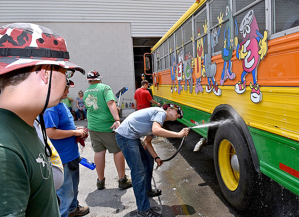 (Brad Davis/The Register-Herald) Scouts from multiple troops out of Illinois begin teaming up to wash the recycling promotional bus at the Raleigh County Solid Waste Authority Thursday afternoon in Beckley.