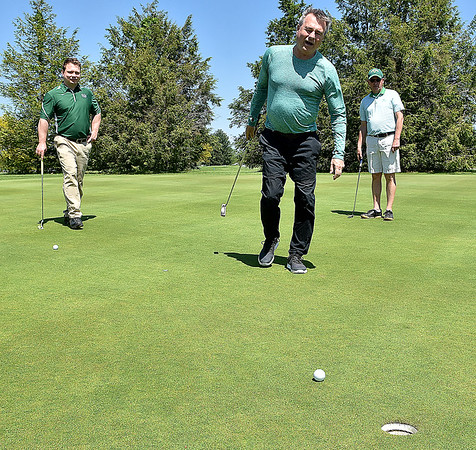 (Brad Davis/The Register-Herald) Mens basketball coach Dan D'Antoni (middle) begs and pleads with his ball, but it keeps rolling wide after a putt as group mates Chris Leister, right, and Chris Grose look on during the 27th Annual Beckley Athletic Club of Marshall University (BAC-MU) Big Green Golf Outing Monday afternoon at Grandview.