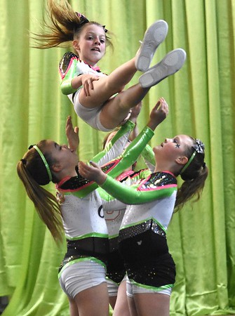 Graclin Tabit, left, Natalie Hunt and Halee, with GymFinity All-Stars team, Galaxy, preparing for a  traveling cheerleading competition.