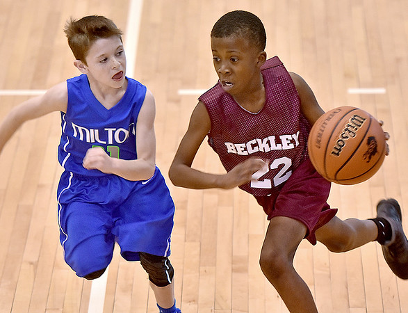 (Brad Davis/The Register-Herald) Beckley All-Stars' Josiah McKay drives as Milton's Carter Womack keeps pace during their fifth-grade Biddy Buddy Tournament game Friday afternoon inside the Van Meter Gym on the WVU Tech campus. Milton won the game 37-27.