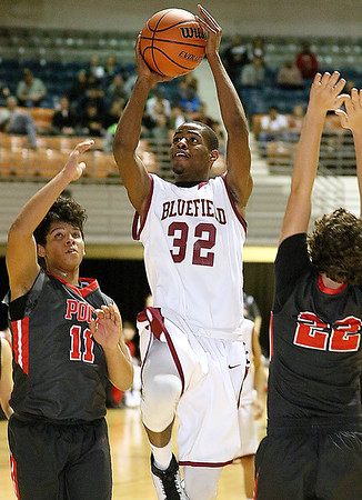 (Brad Davis/The Register-Herald) Bluefield's JaHeem House drives and scores as Poca's R. Jackson McBride, left, and Moah Luikart, right, defend during Big Atlantic Classic action Saturday afternoon at the Beckley-Raleigh County Convention Center.