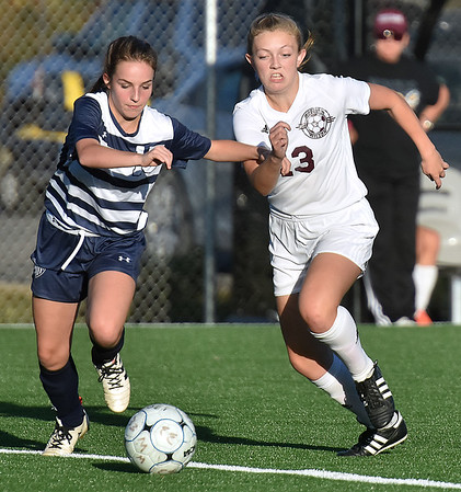 (Brad Davis/The Register-Herald) Woodrow Wilson's Madelyn Grimmett battles for possession with Spring Valley's Reagan Doak Thursday evening at the YMCA Paul Cline Memorial Sports Complex.