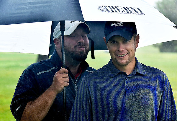 (Brad Davis/The Register-Herald) Brandon Reece, right, thinks it's just a nice photo but groupmate Jeff Miller thinks otherwise as they wait out some rain during BNI action Saturday afternoon at Grandview Country Club.