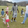 (Brad Davis/The Register-Herald) Former West Virginia running back Noel Devine joins in the chaos as he helps youngsters find eggs during a Spring League halftime Easter egg hunt Sunday afternoon in White Sulphur Springs.