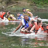 (Brad Davis/The Register-Herald) Participants struggle to steer and hold back laughter as teams labor through the Greenbrier during a six-man canoe race, the main event of a day of canoe races in several categories Sunday afternoon in Alderson as part of the town's 4th of July Celebration.