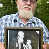 "(Brad Davis/The Register-Herald) Arnold Lilly holds the photo taken when was just four in which he was photographed tugging the beard of the late ""Uncle"" Pleasant Lilly, who was 102 at that time."