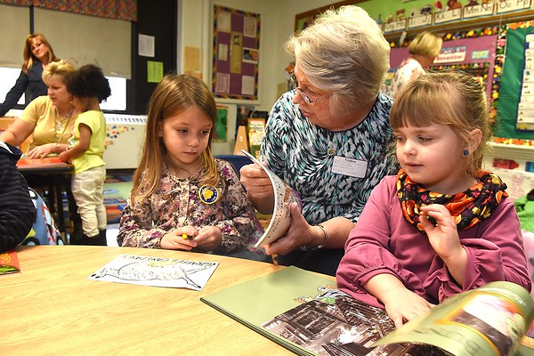 Linda Cole, co-president Fayette Co. chapter Read Aloud West Virginia, center, interacts with, Adalee Crawford, left and Kelly Branstetter, pre-k students in Andrea Martin's class during the Snuggle & Read program held at Mount Hope Elementary School Wednesday morning.<br /> (Rick Barbero/The Register-Herald)