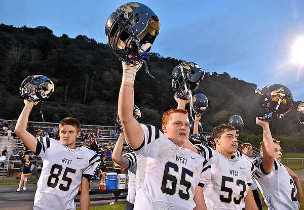 (Brad Davis/The Register-Herald) Greenbrier West players hold their helmets up at the kickoff of their game at Summers County Friday night in Hinton.