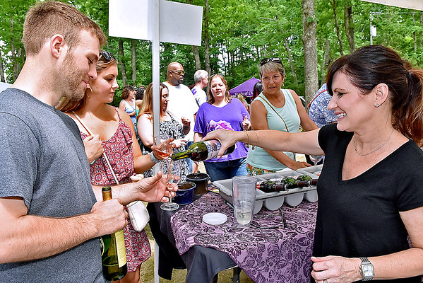 (Brad Davis/The Register-Herald) Lambert Vintage Wines' (Weston, WV) Christina Kurzrock pours samples for Tyler Bennett, currently a Seattle, Washington resident but a Beckley native, and Katie Kramer, an Arlington, Virginia resident and also a Beckley native during Daniel Vineyards' Spring Wine Festival Saturday afternoon in Crab Orchard.