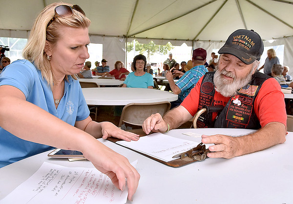 (Brad Davis/The Register-Herald) Mara Boggs, State Director for Senator Joe Manchin, gets some info from Vietnam vet Steve Davis after he raised concerns on the state of the V.A. and his own encounters with agent orange while serving during a town hall meeting at the State Fair Aug. 18 in Fairlea.