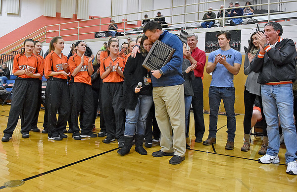 """(Brad Davis/The Register-Herald) Former Summers County Lady Bobcats basketball coach Wayne Ryan, middle in blue, receives a special plaque from principal Kari Vicars surrounded by his family, friends, current and former players during a court dedication ceremony in his name Friday night in Hinton. It will now be known as the """"Coach Wayne Ryan Court."""""""