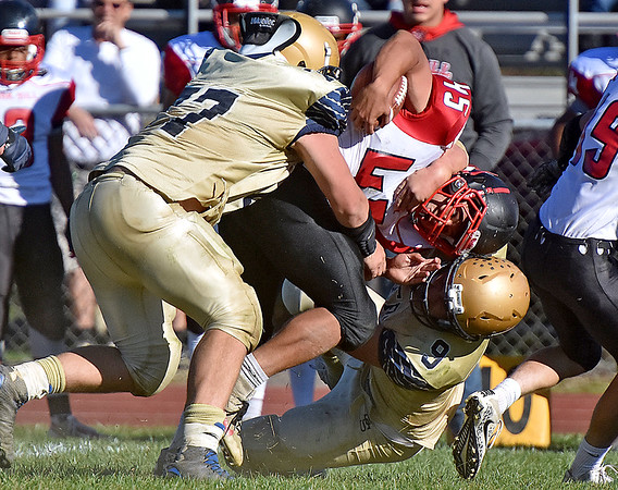 (Brad Davis/The Register-Herald) Oak Hill ball carrier Ta'than Gray is wrestled down by Shady Spring defenders Terymykal Alexander, left, and Jaron Bragg Saturday afternoon.