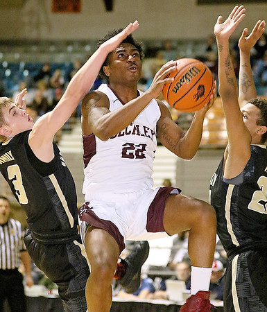 (Brad Davis/The Register-Herald) Woodrow Wilson's Isaiah Francis soars to the basket between University's Kaden Metheny, left, and Storm Leftridge during Big Atlantic Classic action Saturday night at the Beckley-Raleigh County Convention Center.