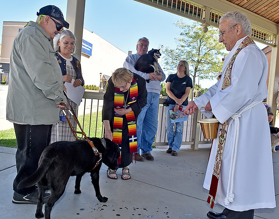 (Brad Davis/The Register-Herald) Nick Fygetakes, left, and wife Laura look on as Rev. Julie Hay Halstead, lead pastor for Raleigh Shared Ministries pets Nick's dog Kepler as he's blessed by Father Adeeb Khalil, ordained minister of the Episcopal faith, during the annual Blessing of the Animals Sunday afternoon under the Word Park gazebo. Kepler serves as a service dog for Nick, who is legally blind.