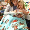 Kim Crist wraps up in a blanket with her daughter Reagan Parker reading her My First ABC book in Andrea Martin's pre-k class during the Snuggle & Read program held at Mount Hope Elementary School Wednesday morning.<br /> (Rick Barbero/The Register-Herald)