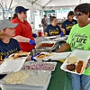 (Brad Davis/The Register-Herald) White Sulphur Springs resident Charlotte Sweeney, right, has her arms full as she gets a couple of plates filled up by Neighbors Loving Neighbors volunteer Amanda Cleghon during Saturday's family fair.