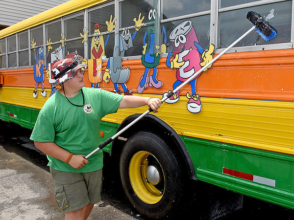 (Brad Davis/The Register-Herald) Illinois Scout Noah Reisetter begins scrubbing down the recycling promotional bus at the Raleigh County Solid Waste Authority Thursday afternoon in Beckley.