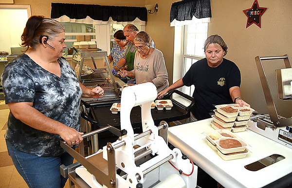 Lisa Vandall, left and Cheryl Persinger, right, are packaging up lunches at the Greenbrier County Committee on Aging in Rupert.<br /> (Rick Barbero/The Register-Herald)