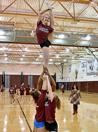 (Brad Davis/The Register-Herald) Coach Laura Zutaut, lower right, watches as Woodrow Wilson cheerleader Allison Shupe (top) and teammates practice stunts during practice at the school Wednesday afternoon.