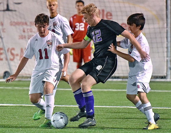 (Brad Davis/The Register-Herald) Riverside captain Brett Murray is harrassed by Woodrow Wilson defenders Ryan Akers, left, and Mathew Randolph Thursday night at the YMCA Paul Cline Memorial Sports Complex.