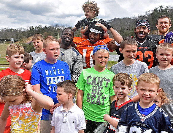 (Brad Davis/The Register-Herald) Former West Virginia receiver J.D. Woods (back row middle) holds up 3-year-old Connor Shea on his shoulders as he and former WVU running back Noel Devine (left of Woods) pose for a massive group photo with young fans and other players following a halftime Spring League Easter egg Sunday afternoon in White Sulphur Springs.