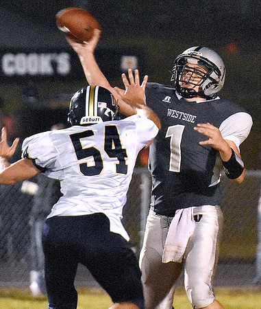 (Brad Davis/The Register-Herald) Westside quarterback Travis Cook throws a deep ball with Nicholas County defender Dawson Blankenship in his face Friday night in Clear Fork.
