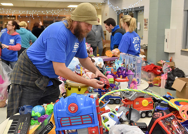 (Brad Davis/The Register-Herald) Wagonwheel Resort co-owner Matt Huggins does his part by volunteering during the Wyoming County Toy Fund Sunday morning at Wyoming East High School. Wagonwheel and RZR Krazy raised around $11,000 for this year's toy fund.