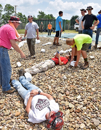 "(Brad Davis/The Register-Herald) Scouts from multiple troops out of Illinois use bodylengths to determined the dimensions for the letters ""RCSWA"" with painted rocks as part of a landscaping project at the Raleigh County Solid Waste Authority Thursday afternoon in Beckley."