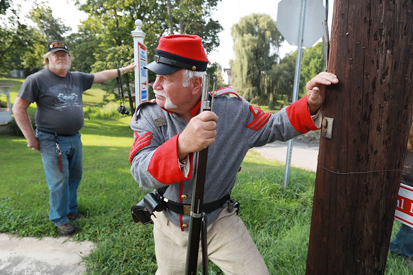Civil War re-enactor Blaine Hypes, from Princeton, hides behind a pole keeping watch on the Federal Army as bystanders look on during a battle between the local Home Guard and the Federal Army as part of Monroe County Heritage Day in Union on Saturday.  (Chris Jackson/The Register-Herald)