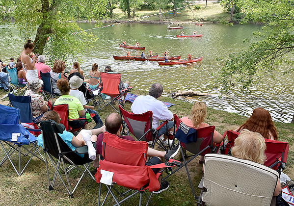(Brad Davis/The Register-Herald) Residents cram the banks at the Alderson boat launch as they take in a day of canoe races in several categories Sunday afternoon in Alderson as part of the town's 4th of July Celebration.