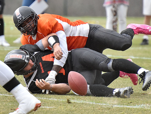 (Brad Davis/The Register-Herald) South (black) quarterback David Ash fumbles the ball as he's hit by North (orange) defensive lineman Ryne Giddins during Spring League action Sunday afternoon in White Sulphur Springs.
