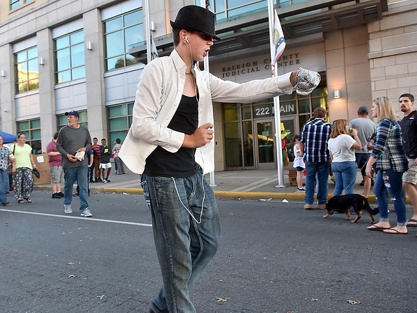 (Brad Davis/The Register-Herald) Greg Hilderbrand moonwalks his way around Main Street as he impersonates the late pop star Michael Jackson during Beckley's annual Chili Night event Saturday evening.
