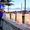 (Brad Davis/The Register-Herald) One by one, Christy Peters, herself honoring the memory of her late grandfather Billy Reece Sr. (1999), lights candles inside special memorial luminaries bearing the names of survivors and those unfortunately lost to cancer during the later moments of the American Cancer Society's Relay for Life atop Beckley's Intermodal Gateway Friday night.