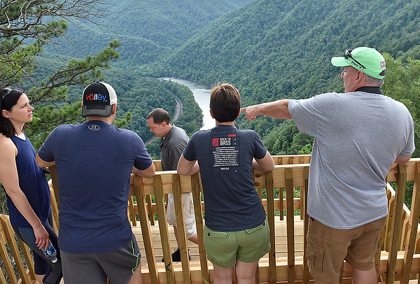 (Brad Davis/The Register-Herald) Some of the first people to get a look from the new Turkey Spur overlooks, including Cincinnati, Ohio residents John Patton at far right and Steve Seeger (3rd from left walking on a lower level) along with Cleveland, Ohio resident Geoff Baron, 2nd from left, take in the view of the New River following a grand opening ceremony for new walkways and decks Friday evening at Grandview Park.