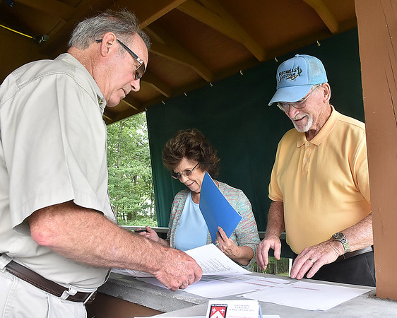 (Brad Davis/The Register-Herald) Paul Holstein and wife Leona Lilly-Holstein dig into their family history with the help of genealogical team member Don WIlliams during the annual Lilly Family Reunion Saturday afternoon near Ghent.