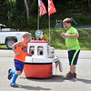 (Brad Davis/The Register-Herald) Four-year-old James Williams, left, and 9-year-old Josh Adkins try to play an impromptu game of tag with Corey the Corps Boat, the Army Corps of Engineers automated water safety mascot Sunday afternoon during Safety on the Blue at Bluestone Lake.